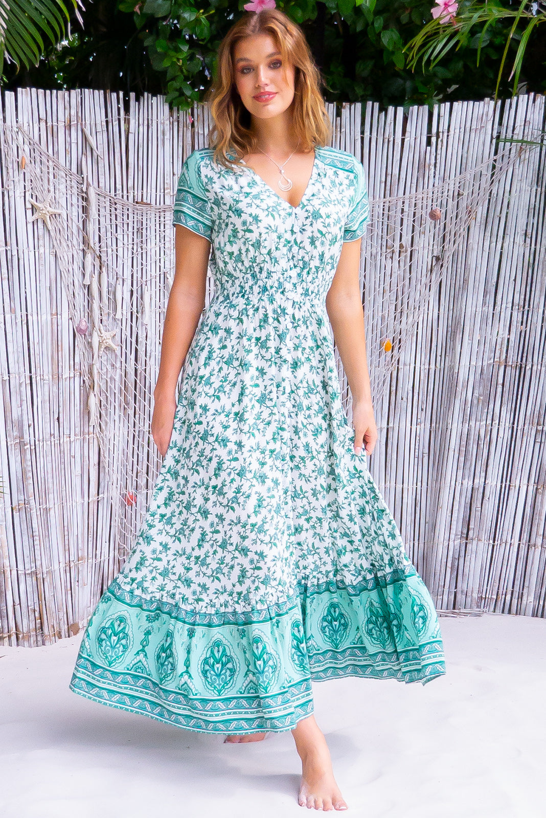The beautiful boho maxi dress, Twilla Fern Green Maxi Dress has functional button front, cap sleeves, elasticated shirred waist, frill hem with border print, white base with intricate mint and green print in woven 100% rayon.