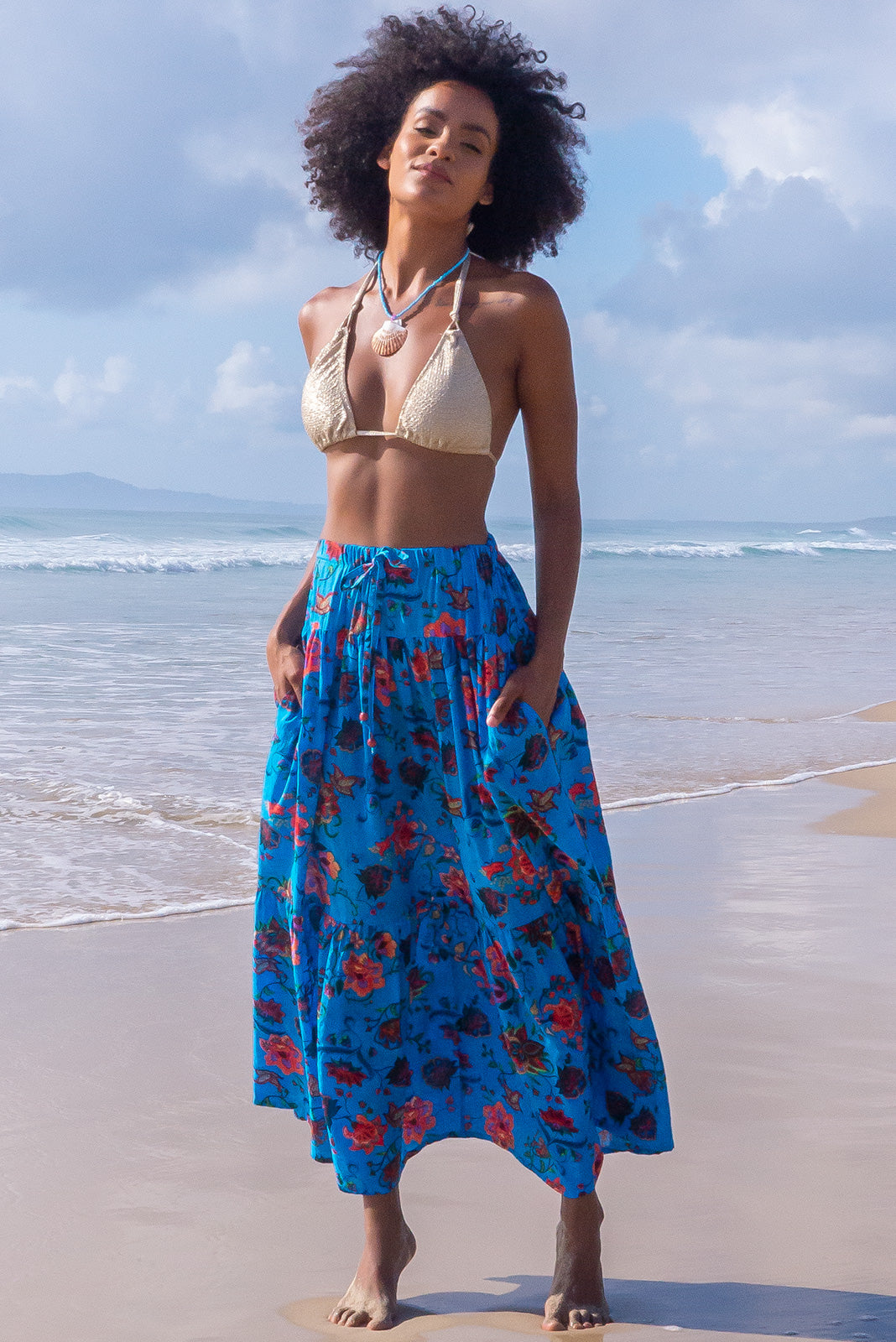 The Valencia Barrio Blue Maxi Skirt is a comfortable slip-on style maxi skirt featuring tiered for fullness, side pockets and cotton/viscose blend in bright blue base with large paisley print.
