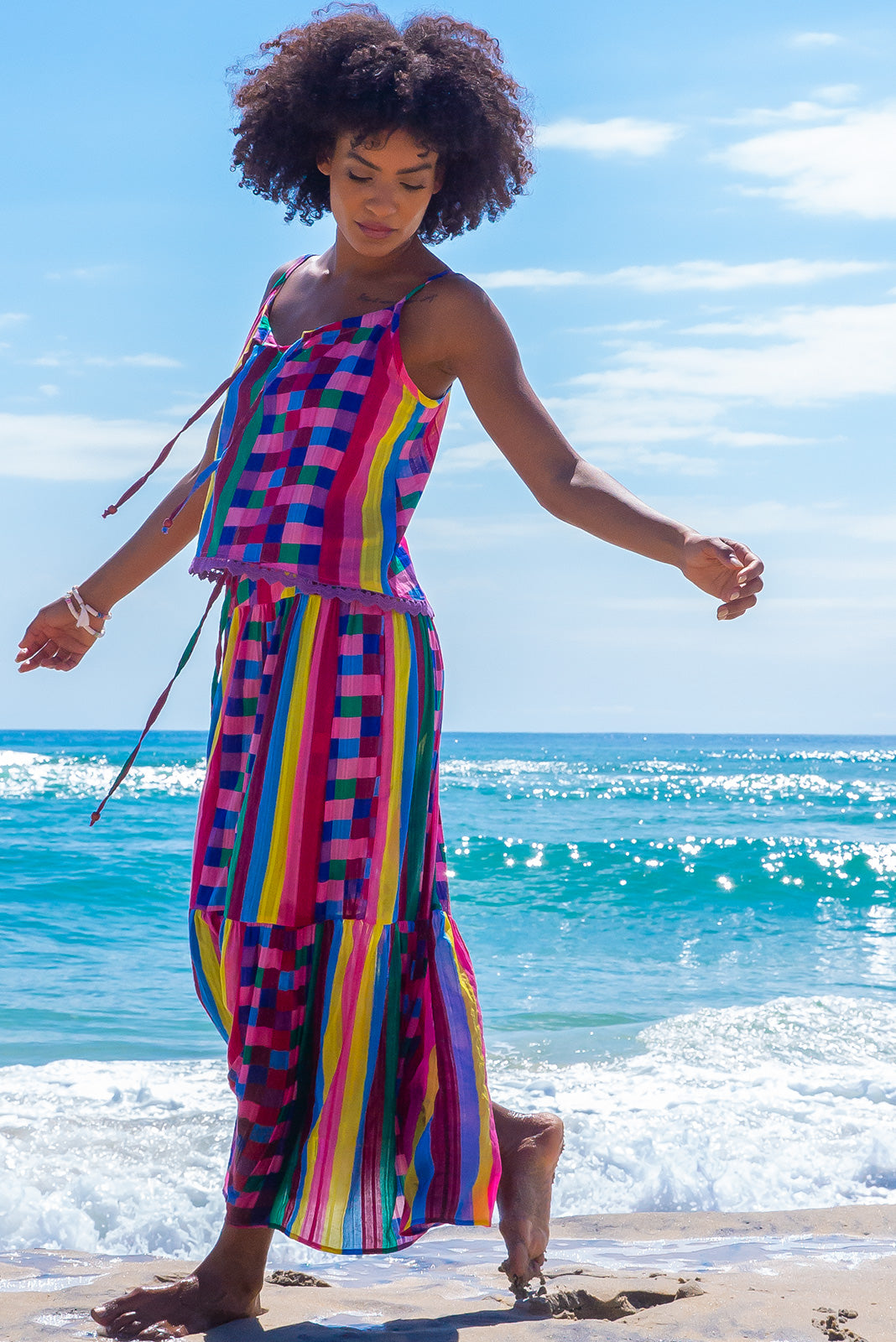 The Valencia Carnivale Maxi Skirt is a vibrant and fun skirt featuring elasticated waistband with decorative tie, side pockets and Woven fabric 95% cotton 5% polyester in vibrant multi coloured check and stripe print with a lurex thread running through.