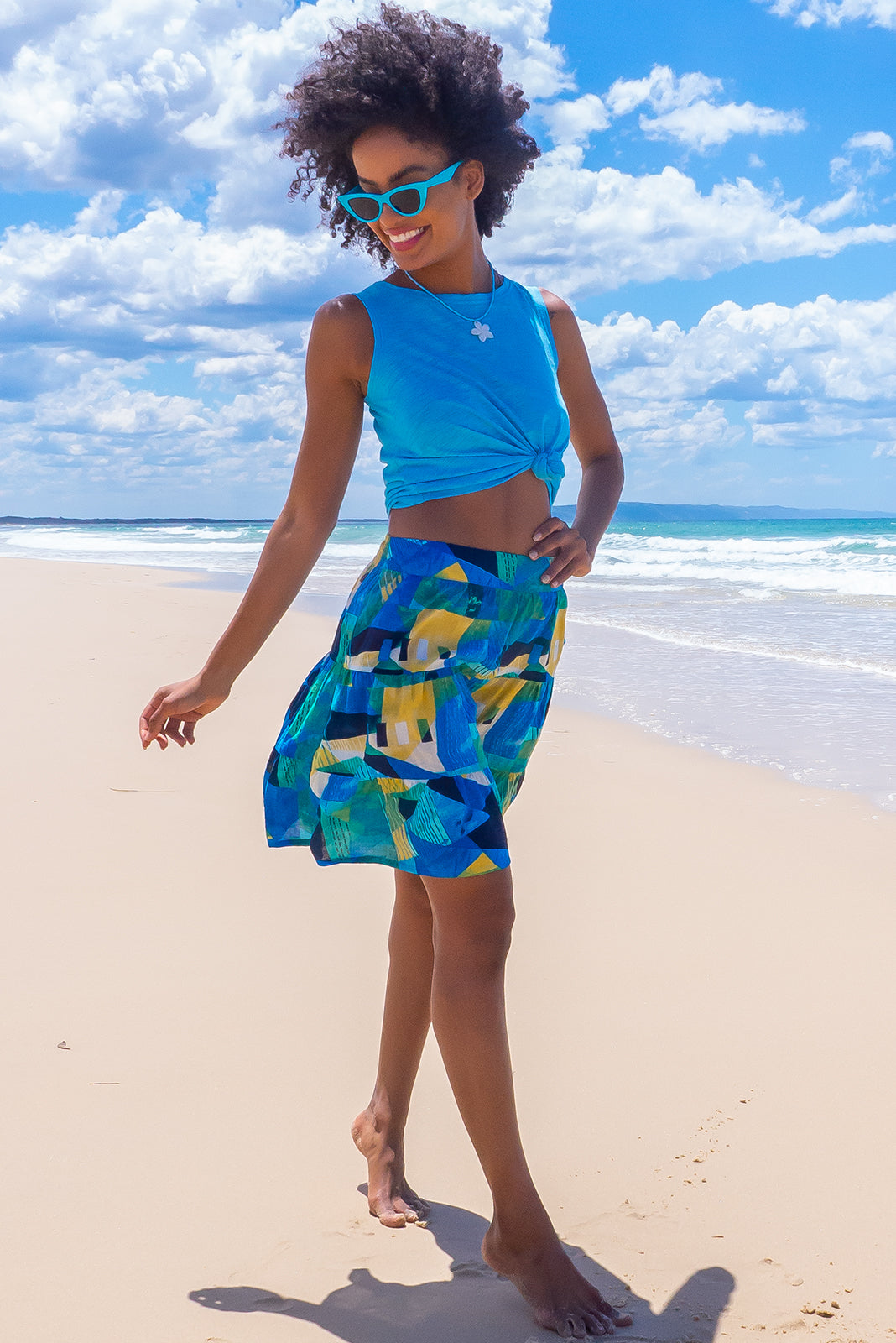 The Valencia Geometric Mini Skirt features elasticated waistband with decorative tie, tiered for fullness, side pockets and 50% cotton, 50% viscose in blue/green geometric print.