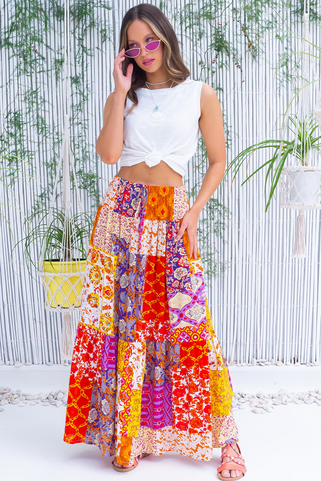 The Valencia Golden Hour Maxi Skirt featurs elasticated waistband with decorative tie, comfortable slip-on style, tiered for fullness, side pockets and cotton, viscose blended fabric in vibrant purple, pink, yellow and orange patchwork print.