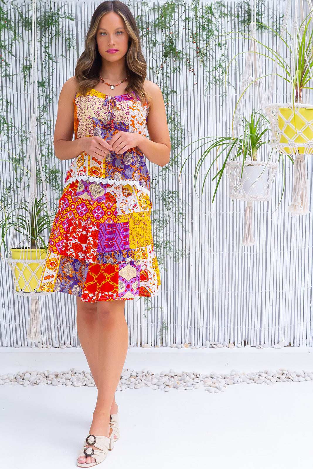 The Valencia Golden Hour Mini Skirt features elasticated back waistband, comfortable pull-on style, tiered for flirty fullness, side pockets and cotton, viscose blended fabric in vvibrant purple, pink, yellow and orange patchwork print.