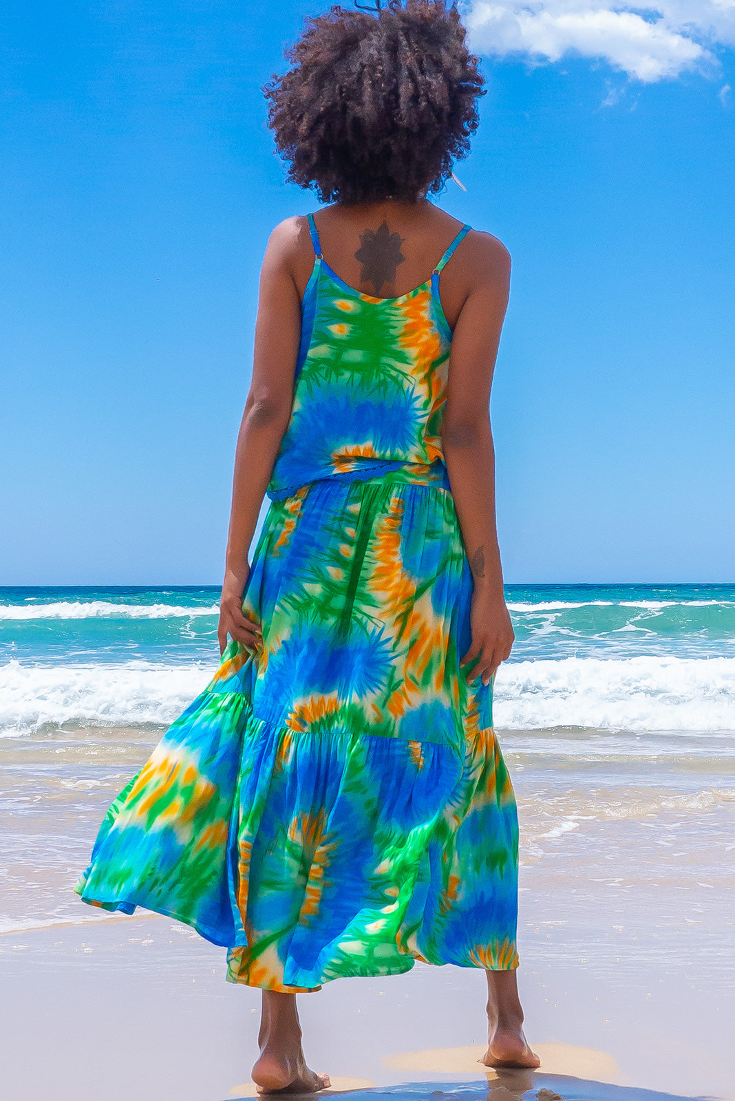 The valencia Ocean Tie Dye Maxi Skirt is a beachy and comfortable slip-on style skirt featuring elasticated waistband with decorative tie, tiered for fullness, side pockets and 100% rayon in tie dye print of blue, green, and yellow.