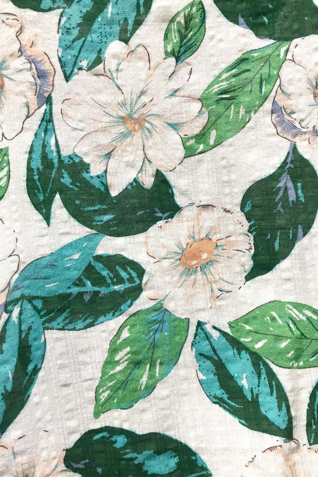 Fabric swatch of Valencia Pearl Flowers Cami Top featuring cotton/viscose blend in white and green floral print.