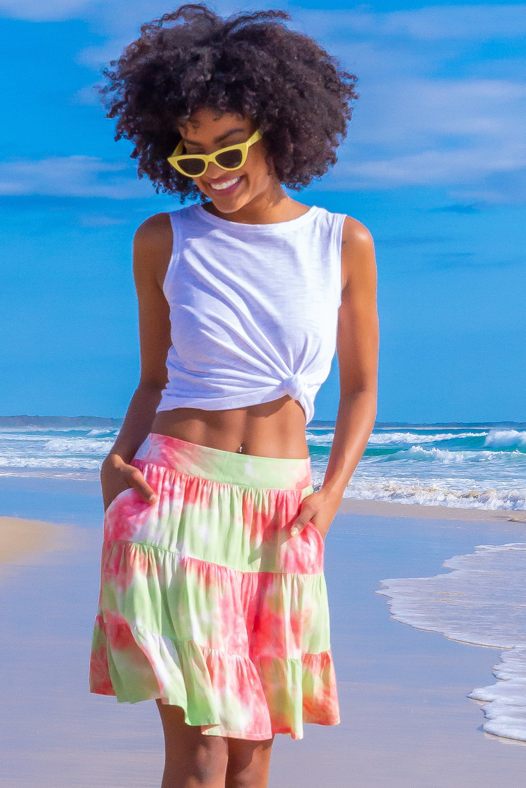 This bright and billowy Valencia Watermelon Tie Dye Mini Skirt features a vibrant pink and mint tie dye print of 100% rayon and has side pockets.