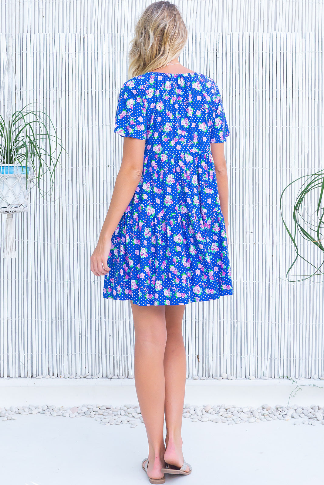The Viva Cobalt Dress features adjustable neckline with tassel ended ties, elasticated back of neckline, short, flutter sleeves, side pockets and 100% rayon in cobalt blue base with pink florals and white polka dots.