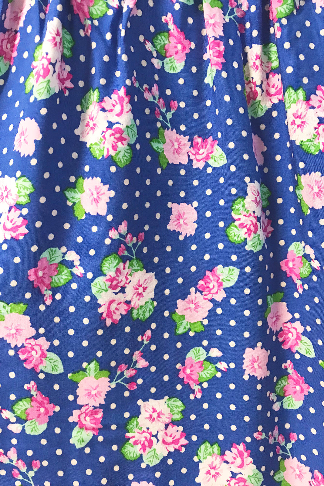 Fabric Swatch of Viva Cobalt Dress featuring 100% rayon in cobalt blue base with pink florals and white polka dots.