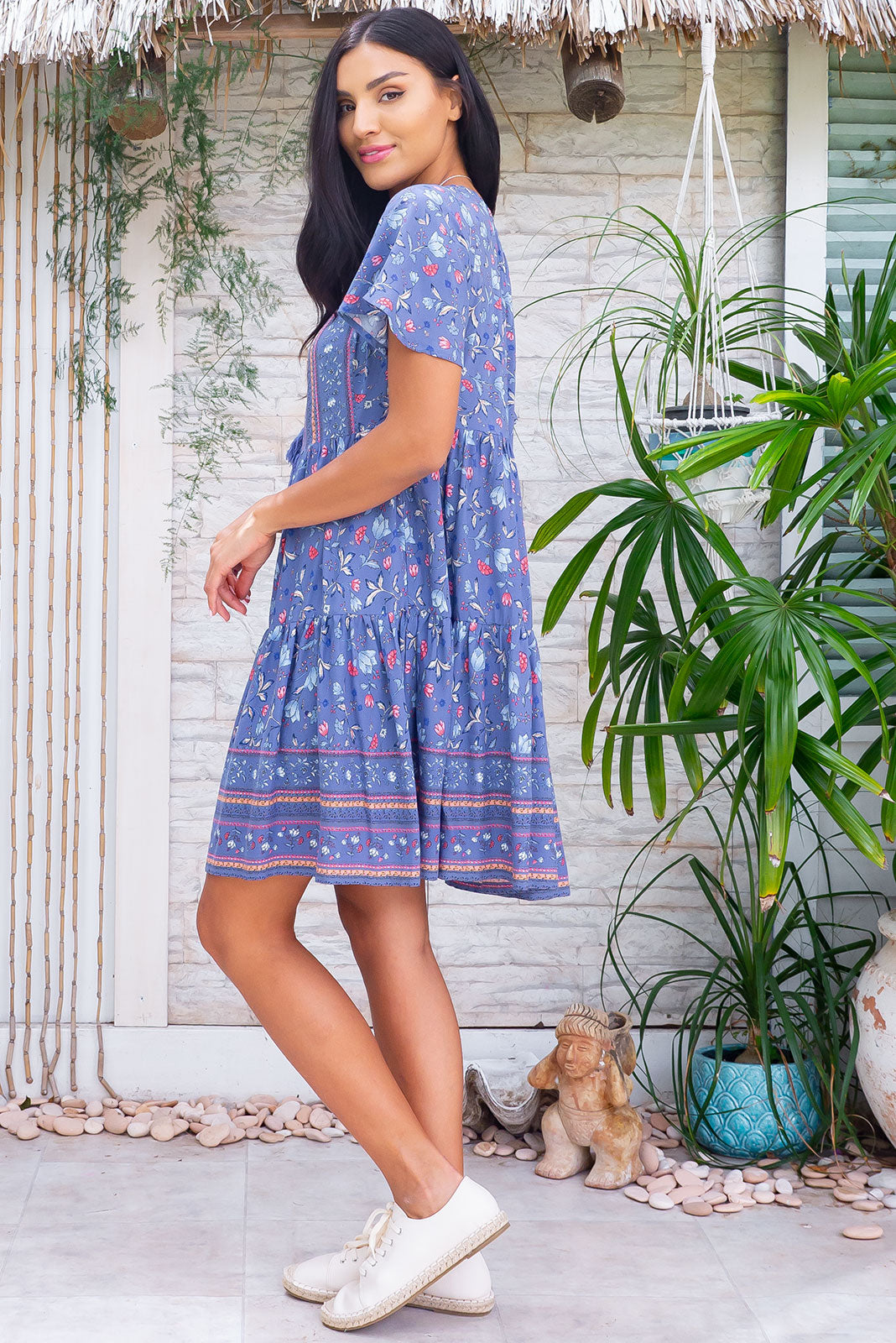 The Viva Highway Blues Dress features adjustable neckline with tassel ended ties, elasticated back of neckline, short, flutter sleeves, side pockets, tiered, full skirt and 100 % rayon in smoky blue base with pretty florals and border feature on chest and hem.