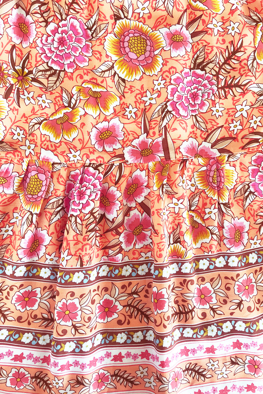 Fabric Swatch of Viva Melon Rose Dress featuring 100% rayon in sherbet orange base with pink, papaya and amber print as well as border feature on chest and hem.