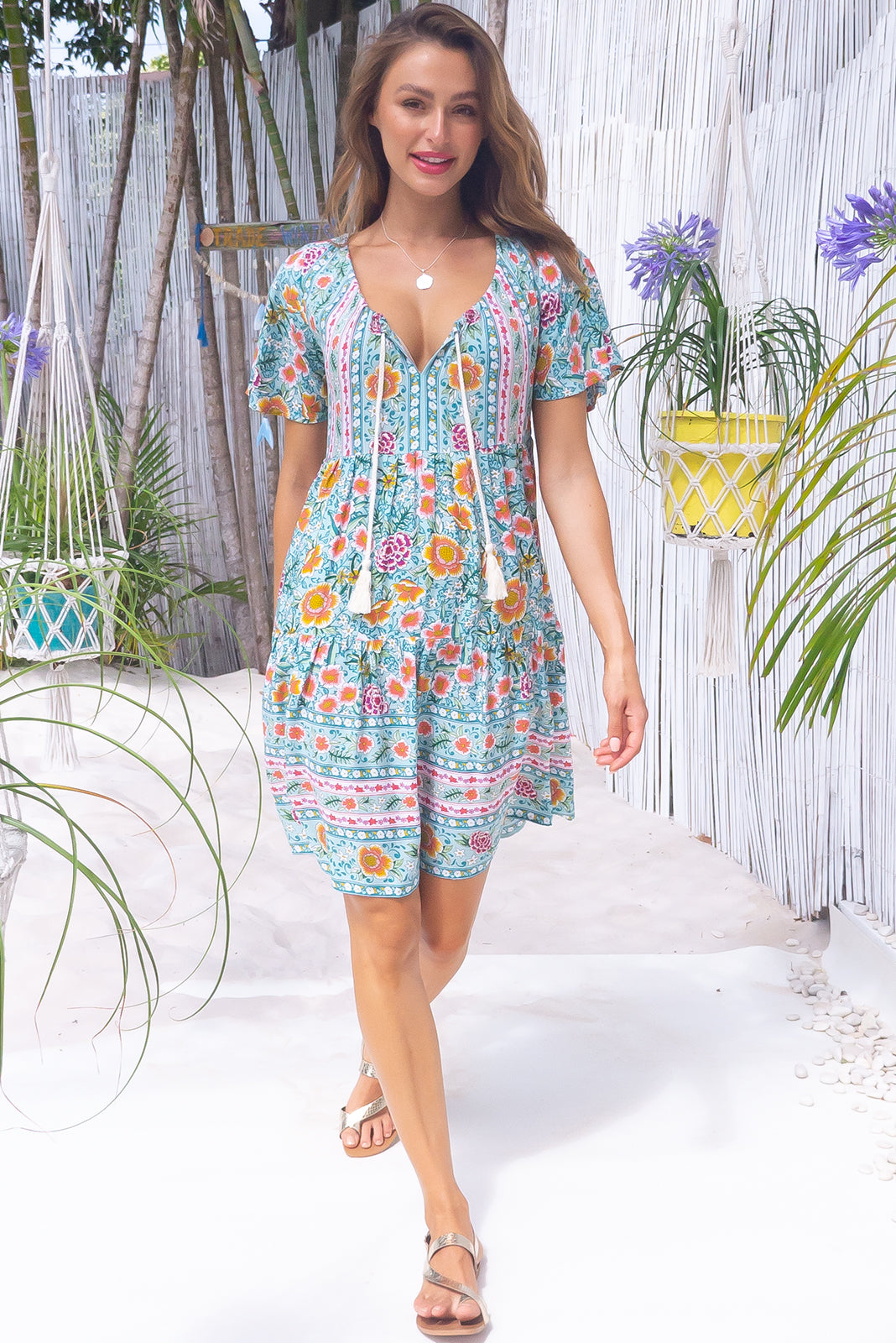 The Viva Mint Tea Dress features adjustable neckline with tassel ended ties, elasticated back of neckline, flutter sleeves, side pockets, tiered skirt and 100% rayon in mint base with pink, green and amber floral print as well as border feature on chest and hem.