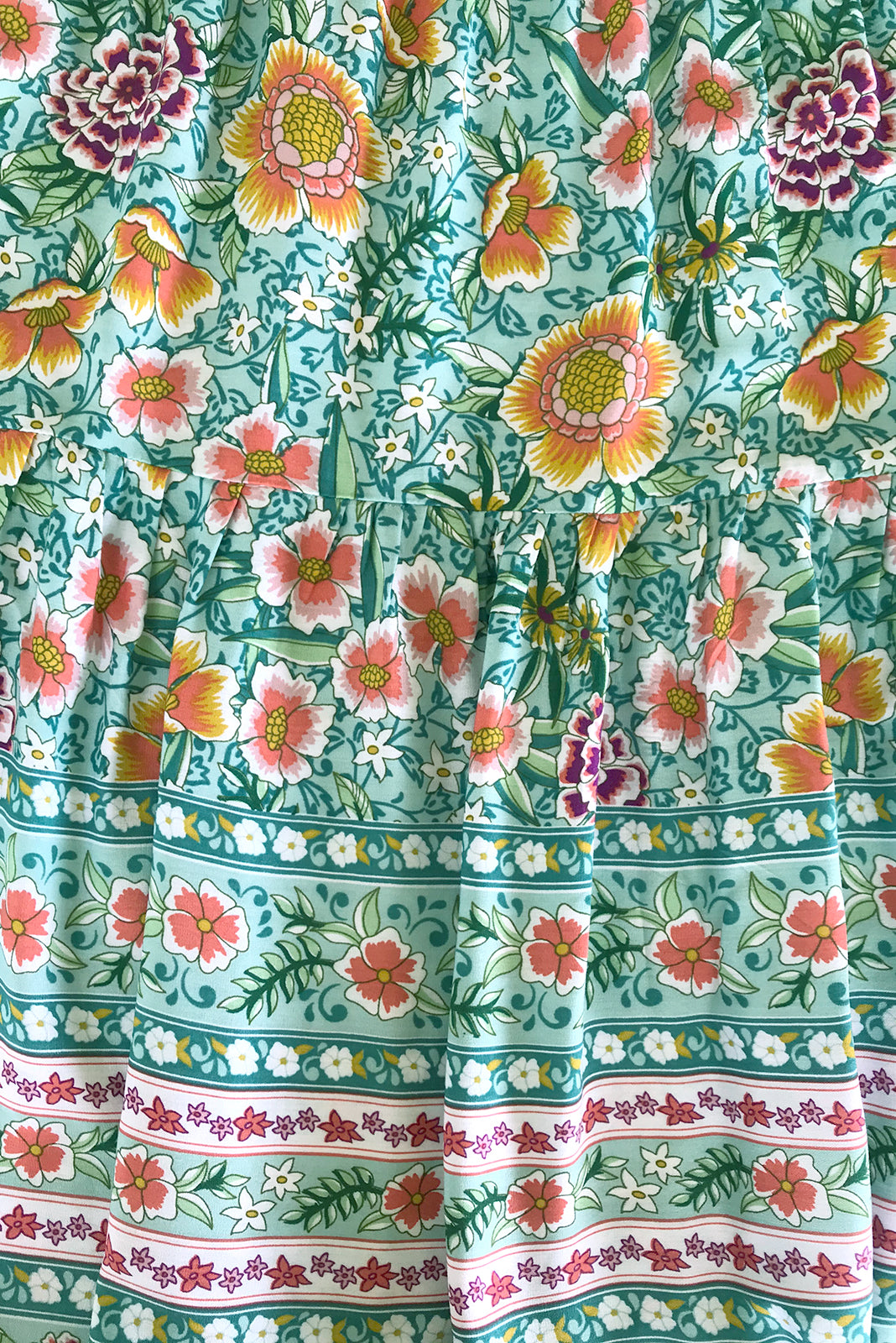 Fabric Swatch of Viva Mint Tea Dress featuring 100% rayon in mint base with pink, green and amber floral print as well as border feature on chest and hem.