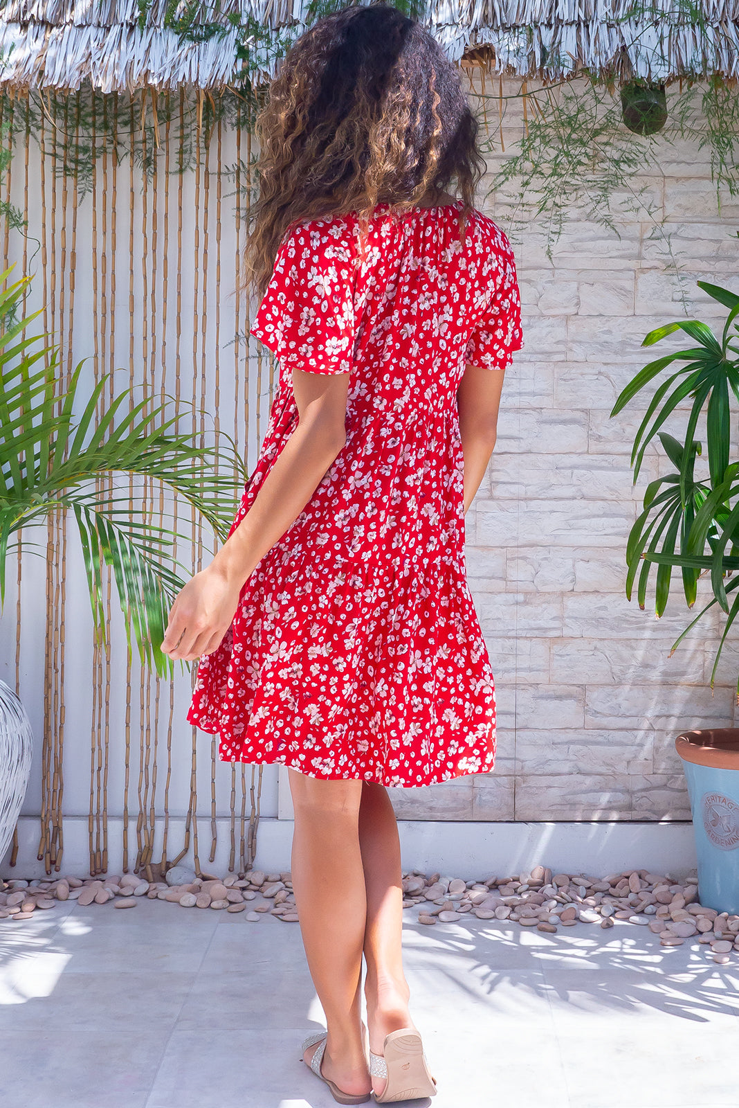 The Viva Ruby Red Dress features adjustable neckline with tassel ended ties, elasticated back of neckline, flutter sleeves, side pockets, tiered skirt and 100% rayon in red floral print.