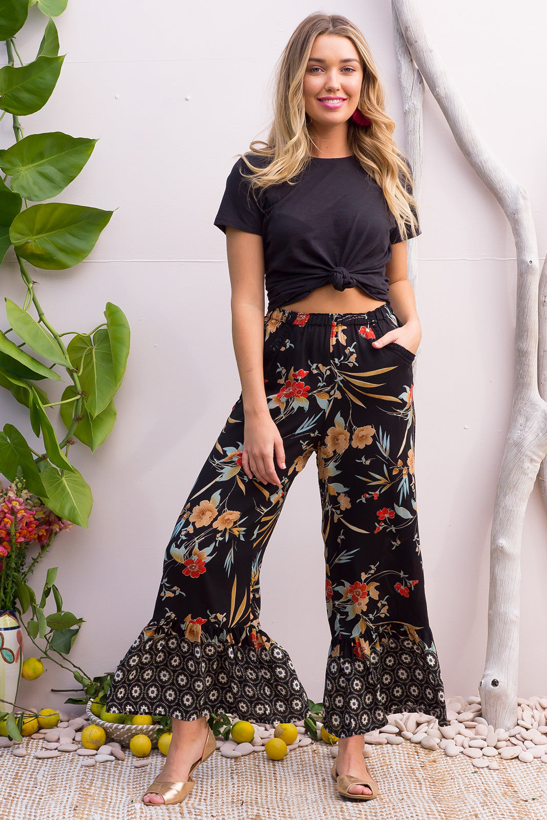 Wandering Pants Tropics Noir  feature a slim leg with a wide frill around the hem for a retro vintage style, the black tropical inspired design is printed onto woven rayon