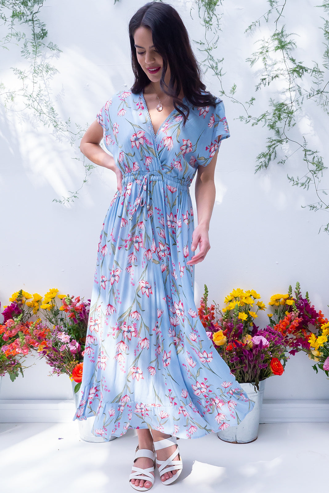 Willow Misty Blue Maxi Dress features V-neck with lace feature, cap sleeves, elasticated waist with decorative tie, frill hem and crinkle textured rayon in sky blue base with floral print.