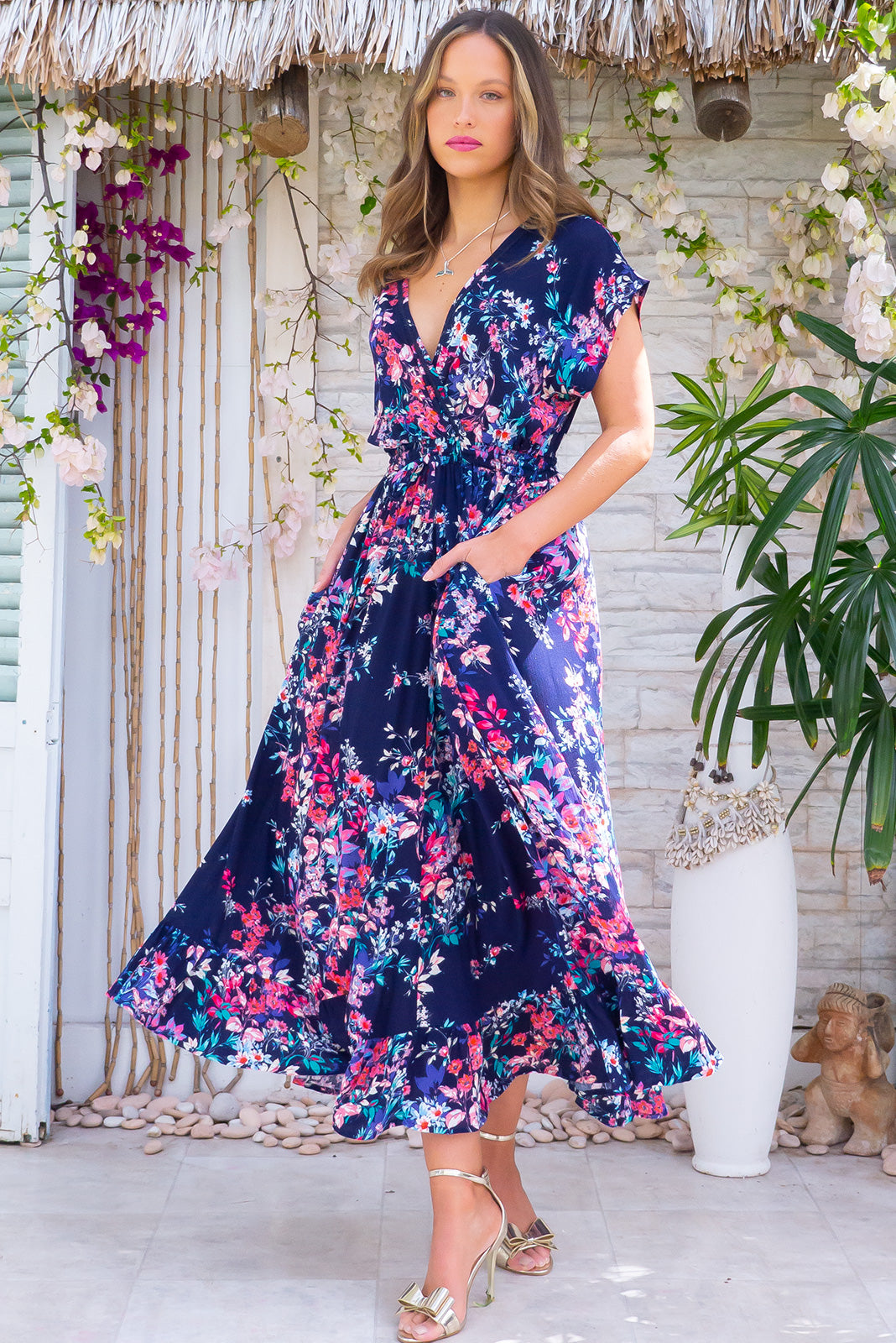 The Willow Navy Splash Maxi Dress features V-neck with lace feature, cap sleeves, elasticated waist with adjustable drawstring, frill hem and Crinkle textured woven 100% rayon in navy base with bright floral print.