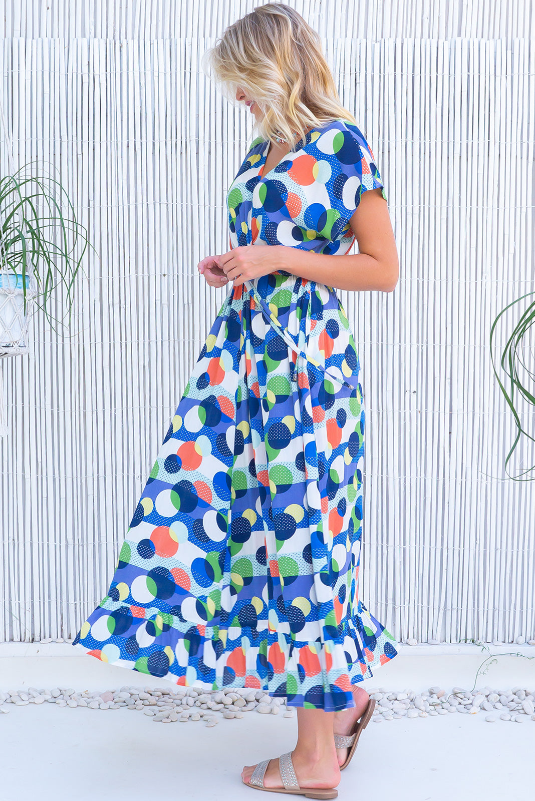 The Willow Spotted On Maxi Dress is a V-neck with lace feature Maxi Dress featuring cap sleeves, elasticated waist with adjustable drawstring, frill hem and crinkle textured 100% viscose in bright, retro spot print in blue, white, navy, orange, yellow and green.