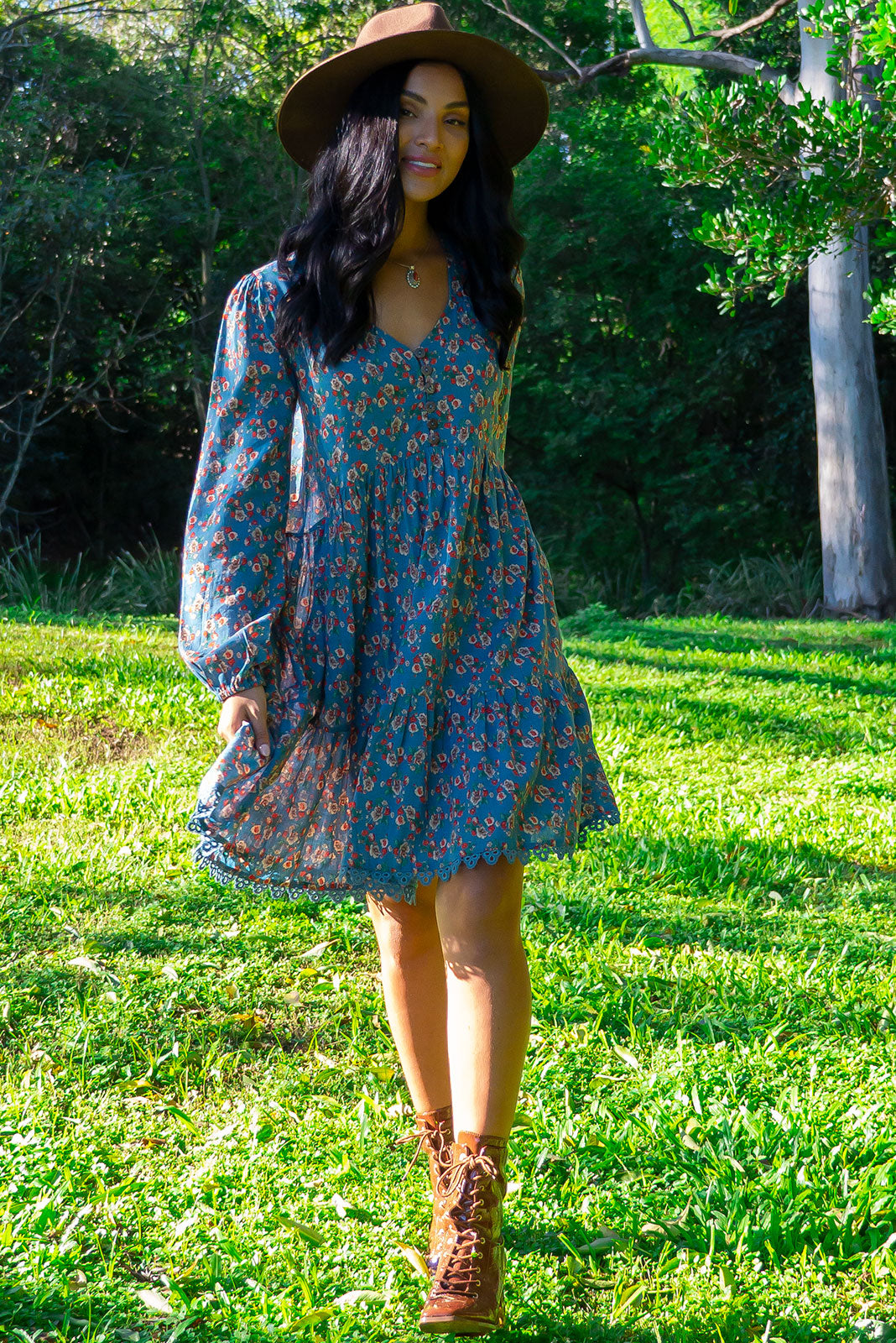 The Woodrose Maleny Meadow Dress is a relaxed fit dress featuring functional button front chest, V-neck, sleeve cuffs are elasticated, side pockets, frill hem, slightly longer at back and cotton/rayon blend in smoky blue base with floral print.