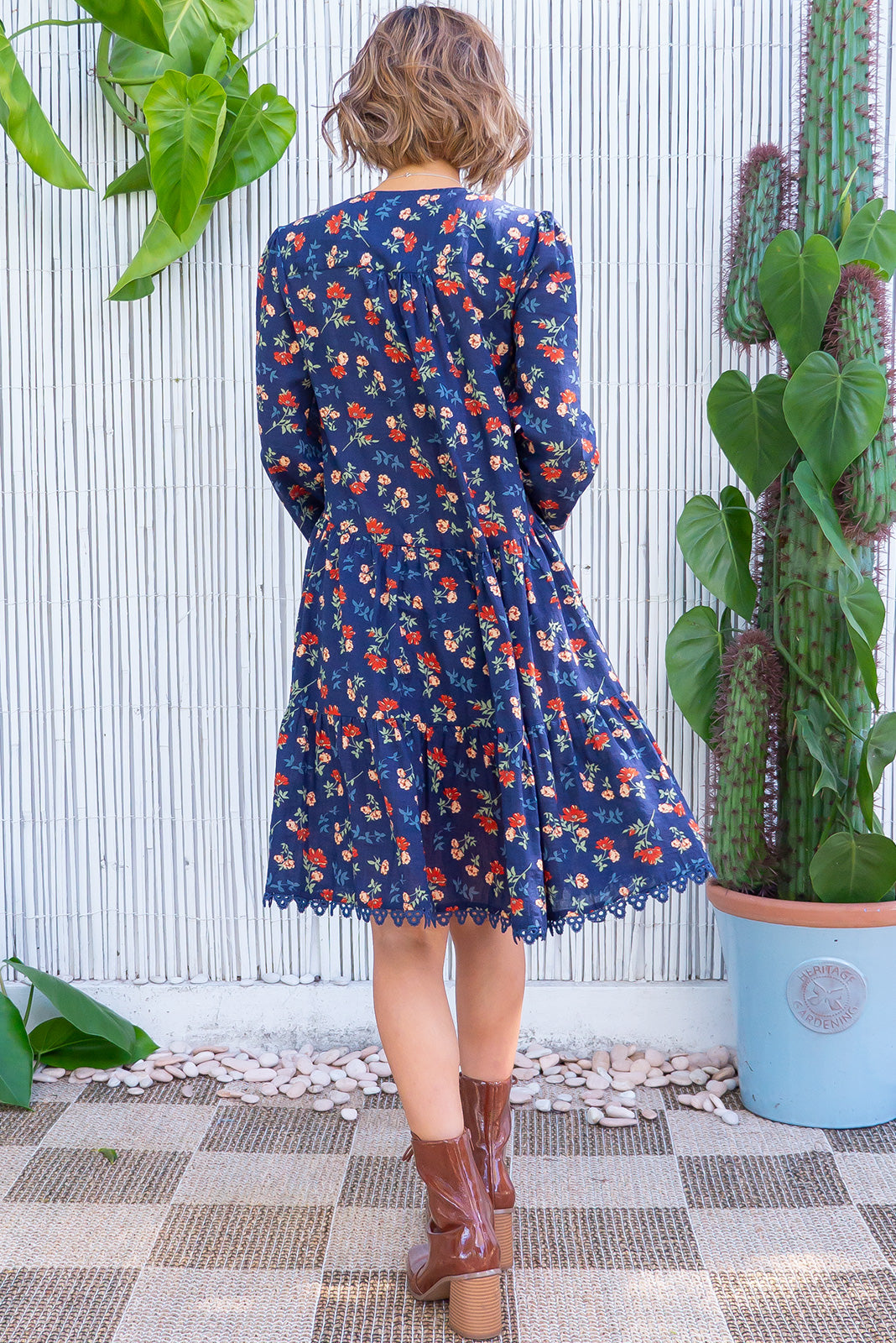 The Woodrose Navy Megs is a relaxed fit mini dress Dress featuring functional button front chest, V-neck, sleeve cuffs are elasticated, side pockets, frill hem, slightly longer at back and cotton/rayon blend in navy base with floral print.