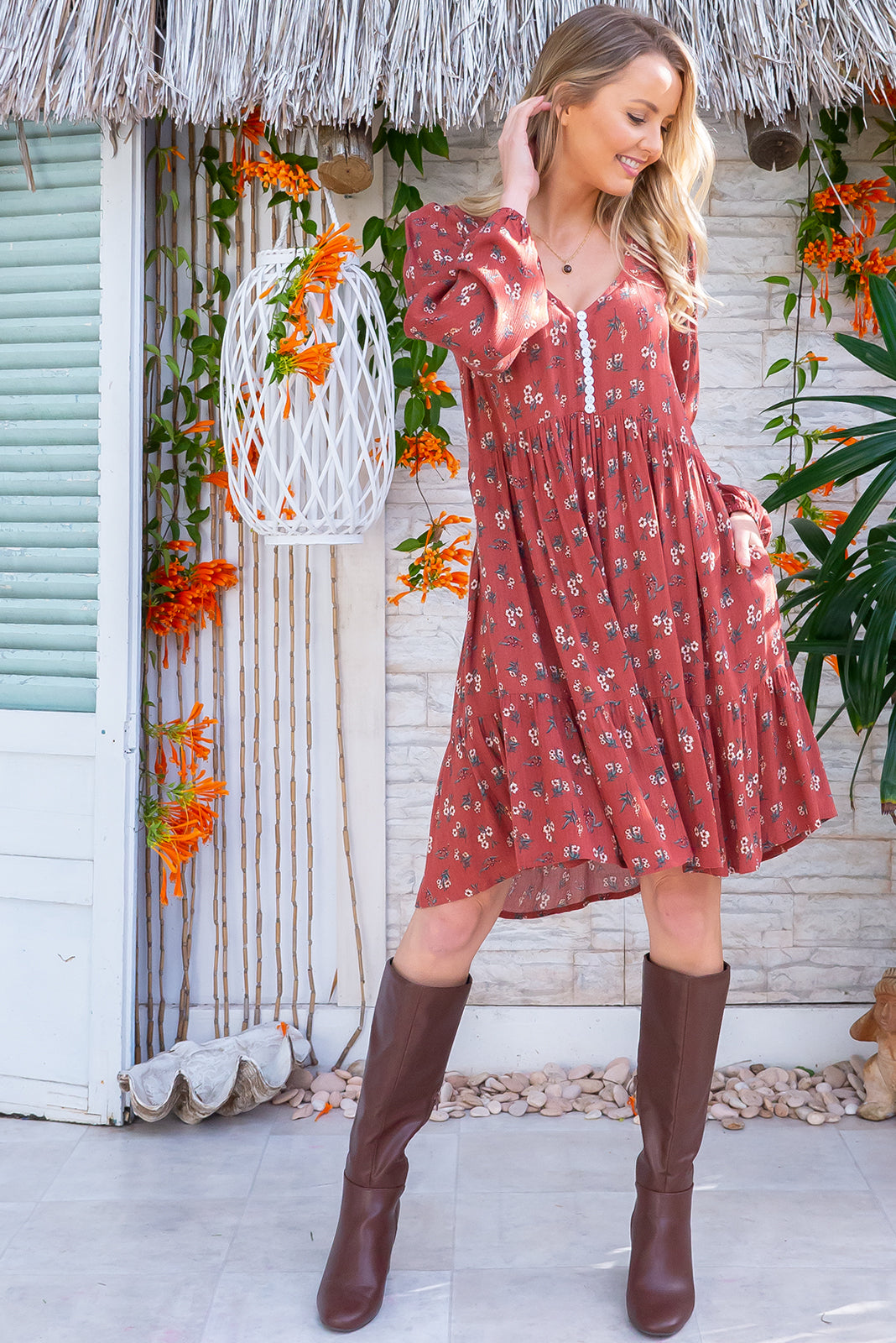 The Woodrose Nutmeg Sprinkle Dress features functional button front chest, side pockets, frill hem and woven 100% crinkle textured rayon in warm, nutmeg base with multi-coloured floral design.