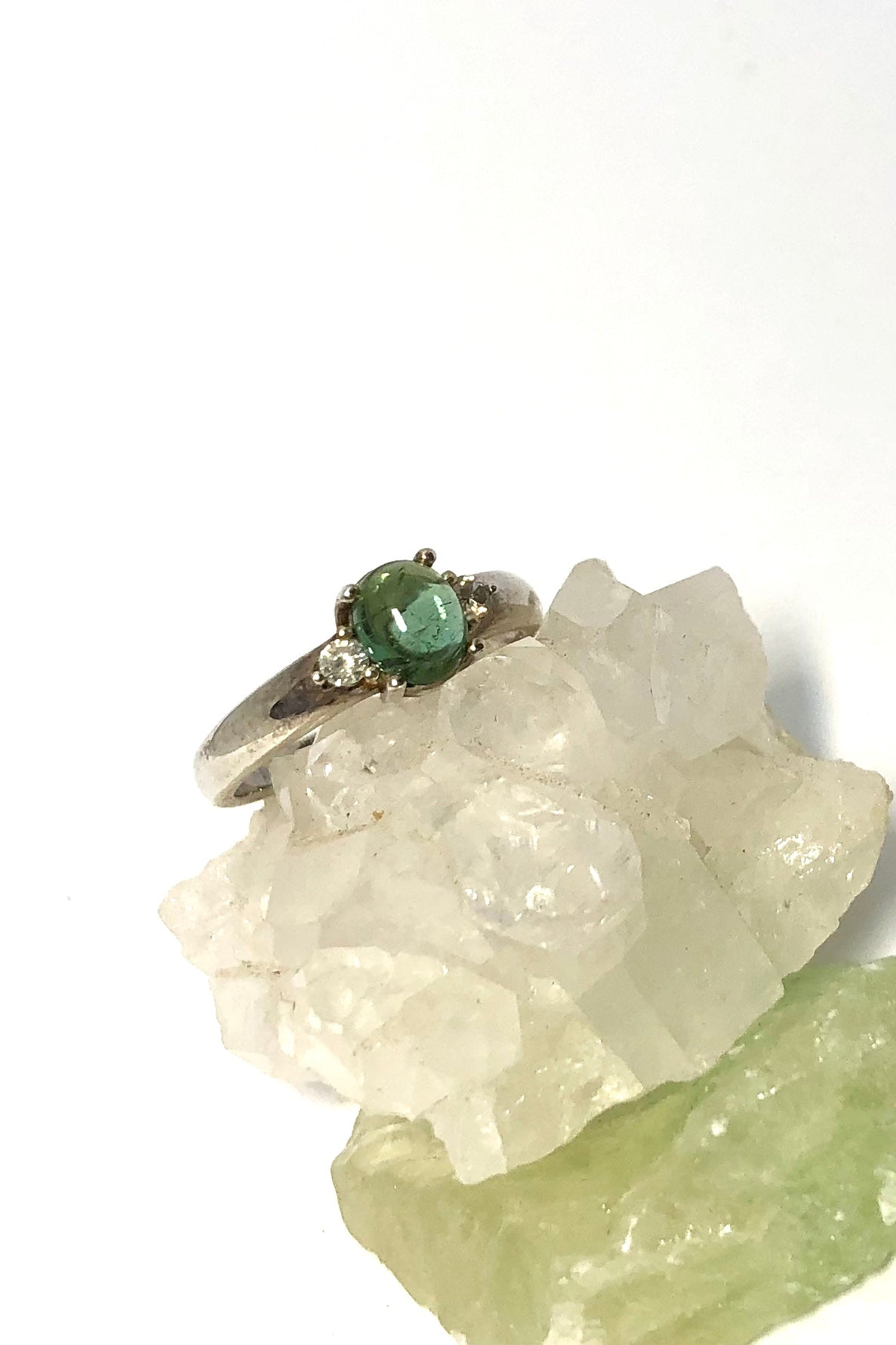 Ring Green Tourmaline with Topaz Side Stones featuring Oval cabochon green tourmaline gem stone, 6/52 small, sterling silver band and modern setting.