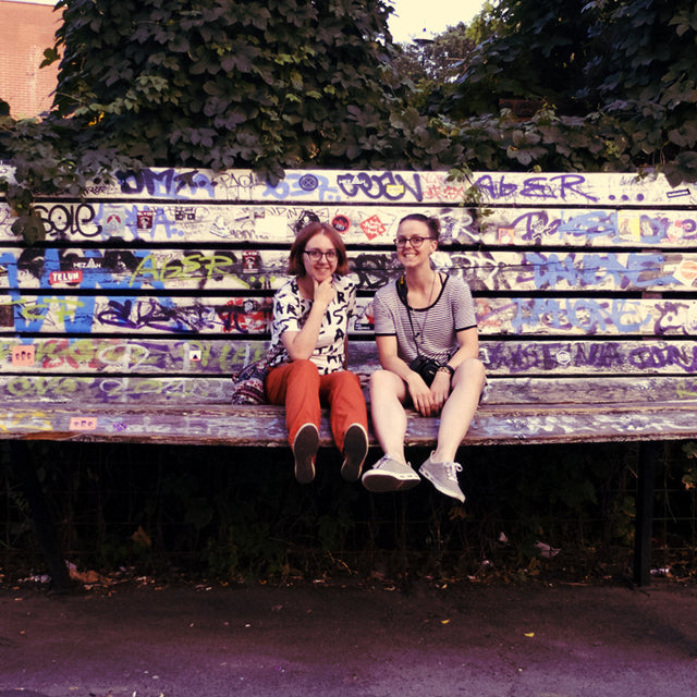 Katrin and Christina, founders of Sharp as Knives, the lifestyle company, are sitting on a massive bench in Berlin, Germany while on one of their many adventures.