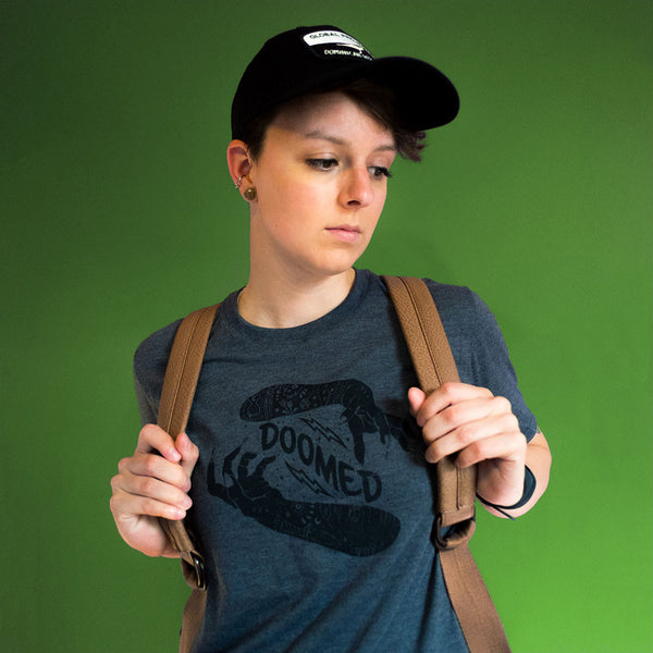 doomed t-shirt streetwear on grey triblend with model wearing backpack and black hat