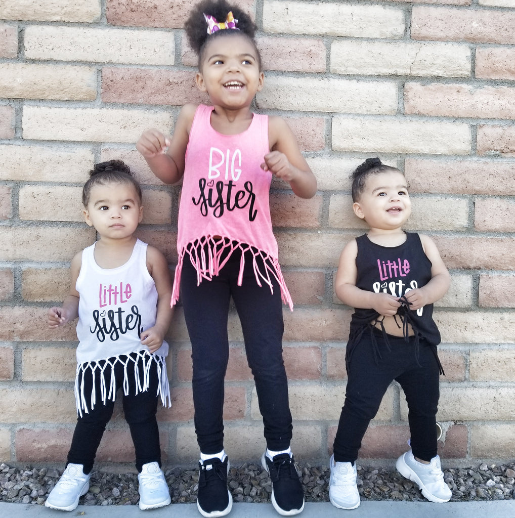 Little girl wearing pink fringe shirt that says Big Sister in white and black with twin toddler girls wearing white and black fringe tanks that say Little Sister in white and pink