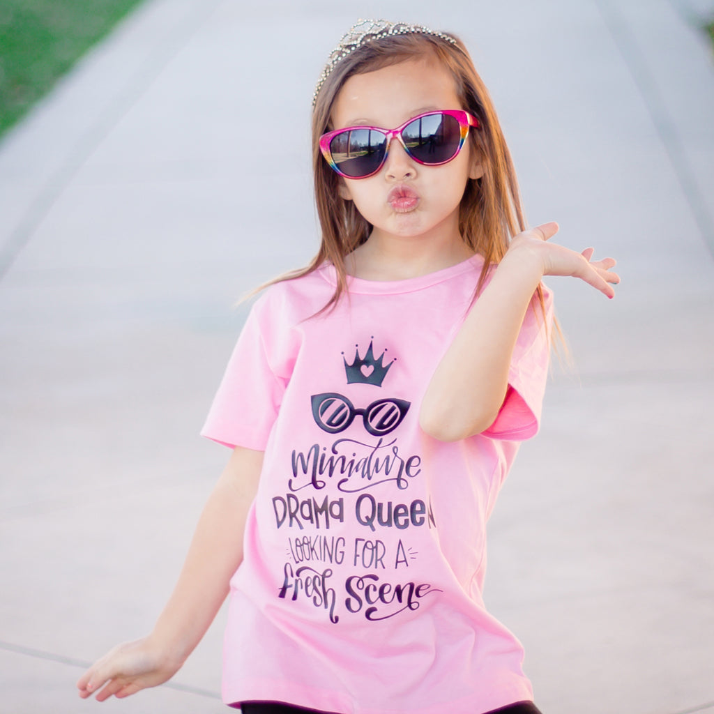 Girl wearing sunglasses, tiara, and a shirt that says miniature drama queen in black