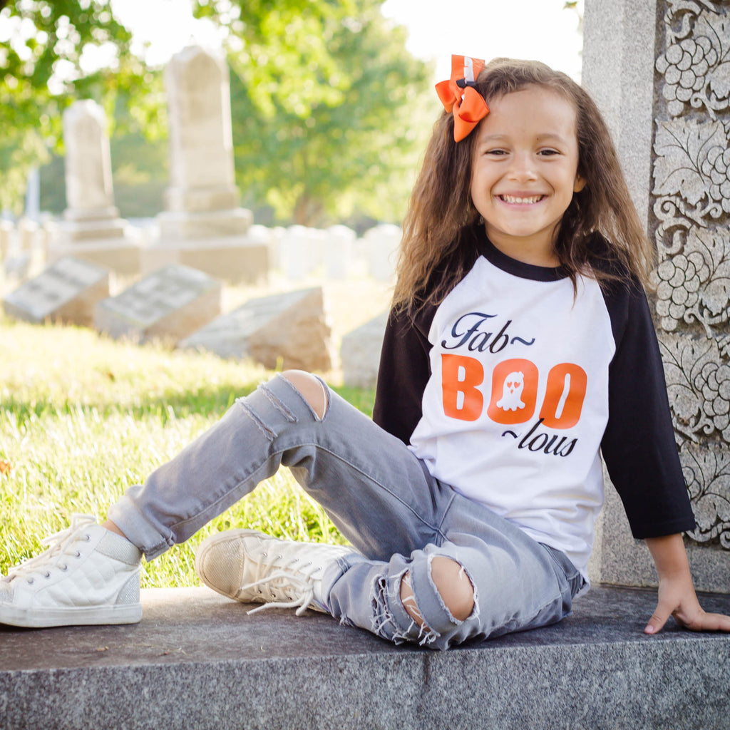 Little girl wearing halloween themed black raglan with FabBOOLous on the front in orange and black