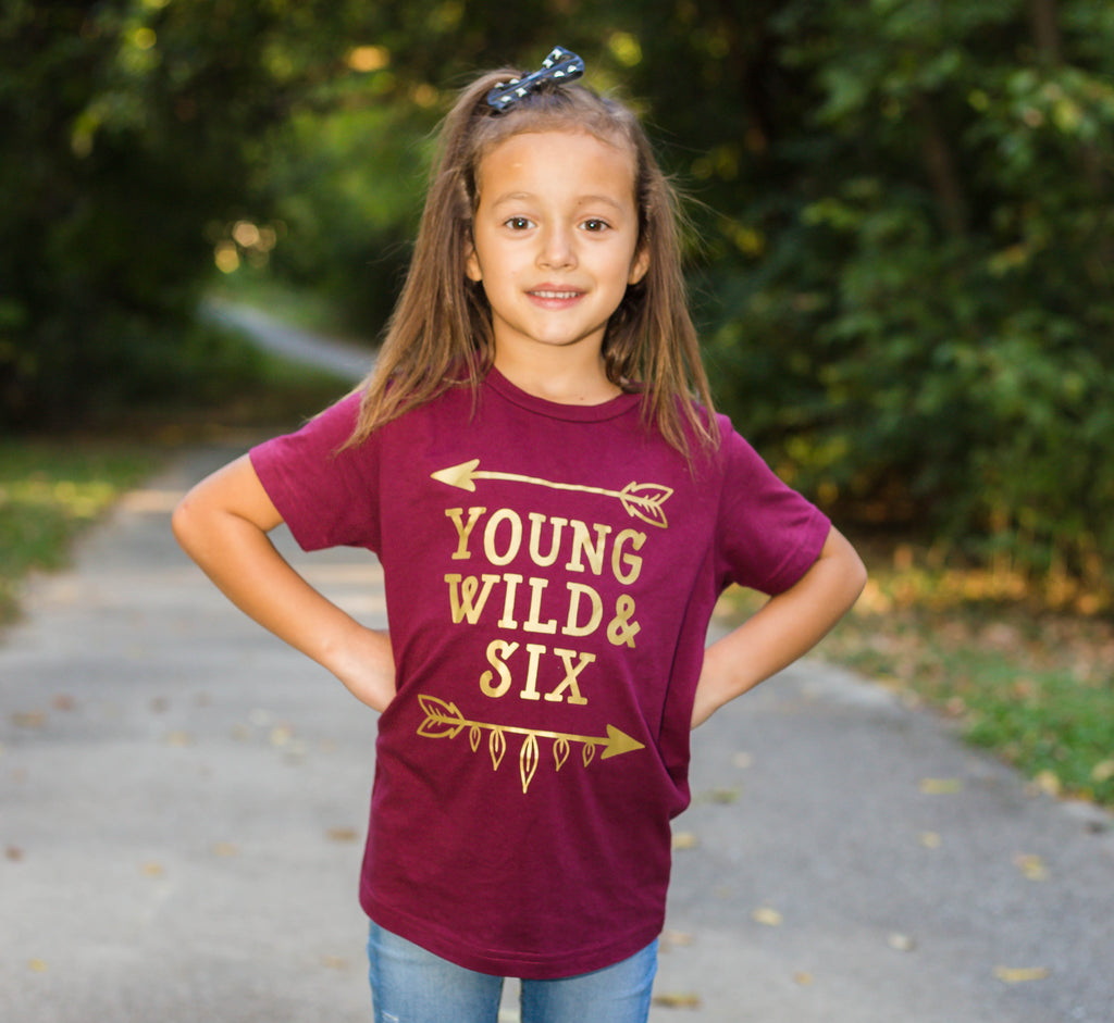 Little girl wearing wine colored shirt with Young Wild and Six in gold with arrows
