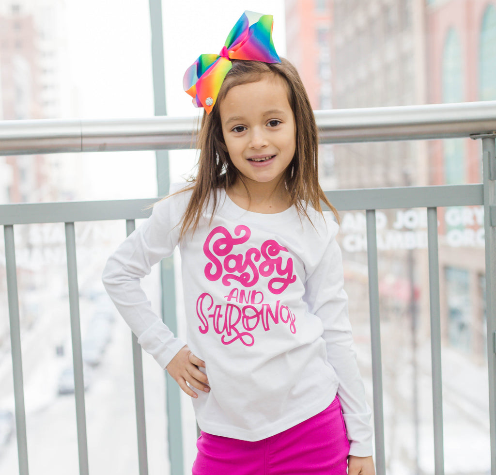 Girl wearing white shirt with sassy and strong written in pink
