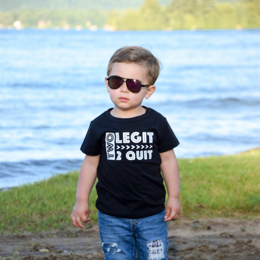 Little boy in front of lake wearing sun glasses and black shirt that says Two Legit 2 Quit in white
