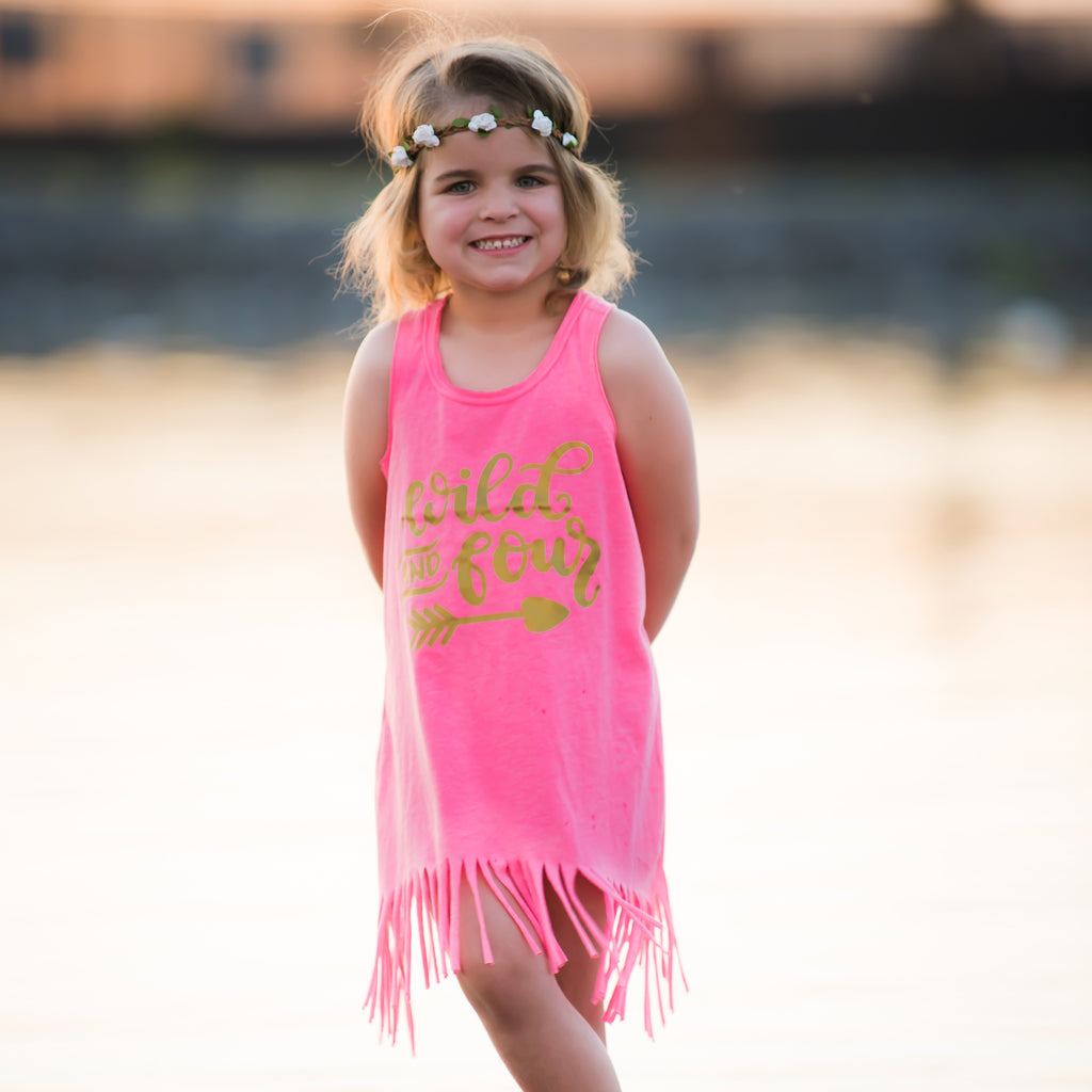 Little girl wearing pink fringe dress that says Wild and Four in gold