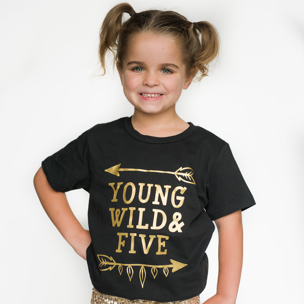 Little girl wearing black short sleeve shirt that says Young Wild and Five with arrow above and below in shiny gold