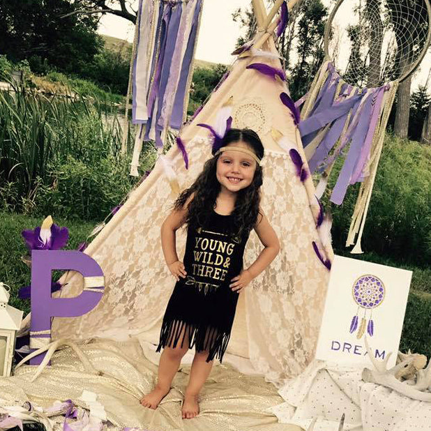 Little girl in front of teepee wearing black fringe dress that says Young Wild and three in gold