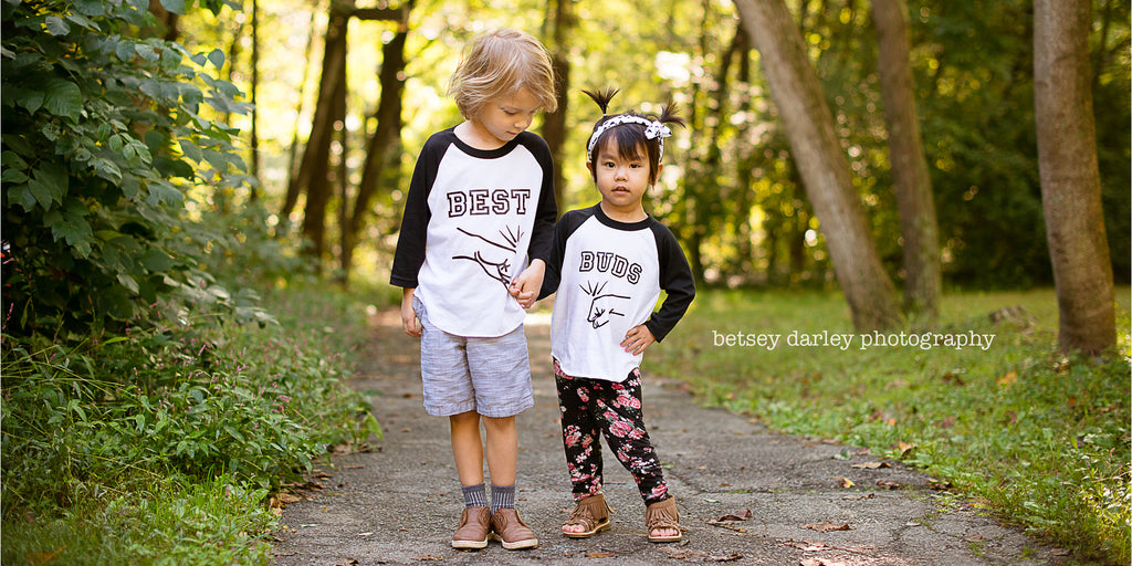 Little boy and little girl holding hand wearing black sleeve raglans that say Best and Buds with fist bumps