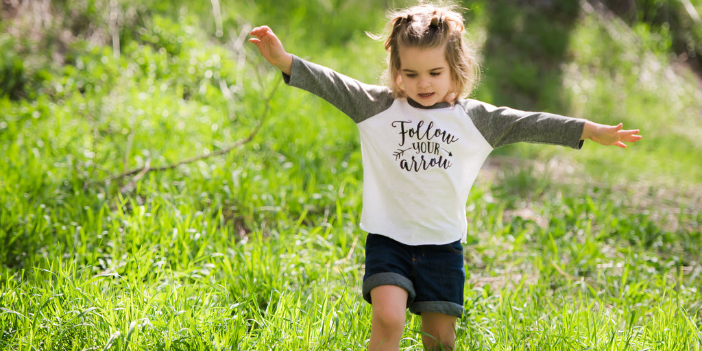Little girl with outstretched arms wearing a grey sleeve raglan that says Follow Your Arrow