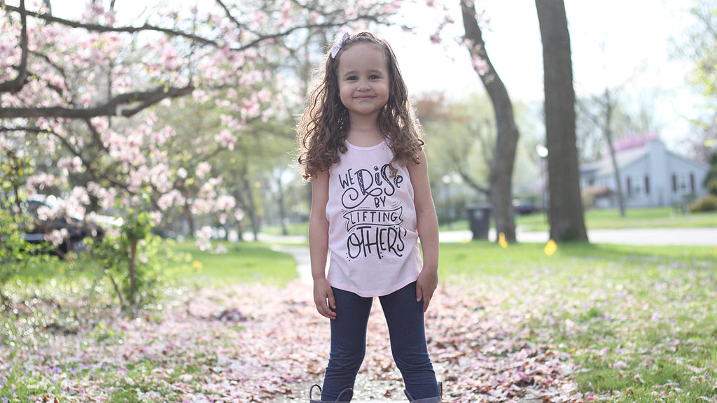 Little girl standing in cherry blossoms wearing pink tank that says we rise by lifting others