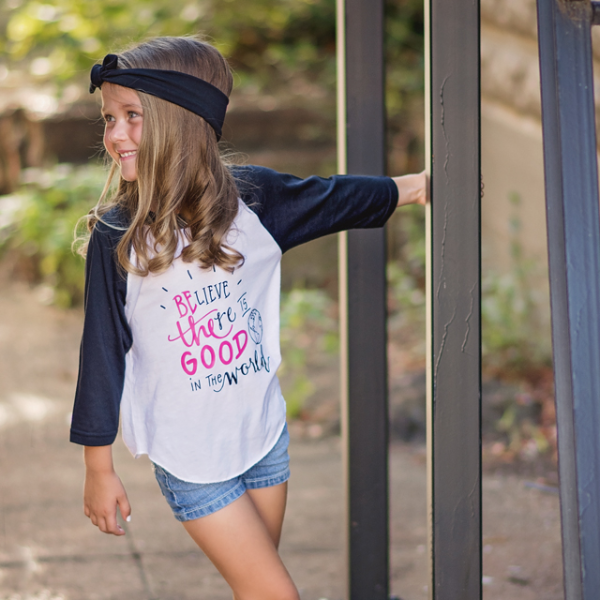 Little girl wearing black sleeve raglan that says Believe There Is Good In The World in pink and black