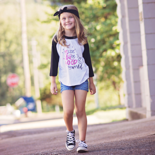 Little girl wearing black sleeve baseball tee that says Believe there is good in the world in black and pink