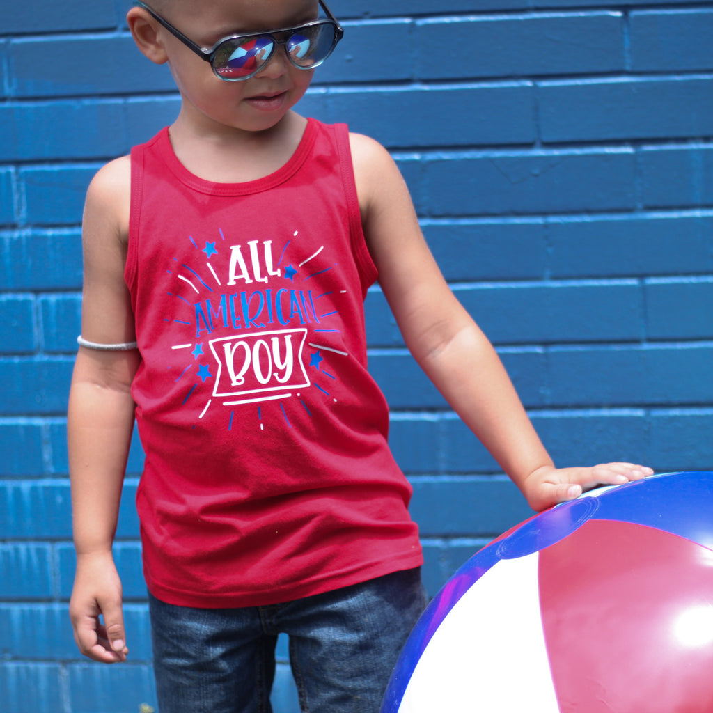 Little boy wearing red toddler tank that says All American Boy in White and Blue