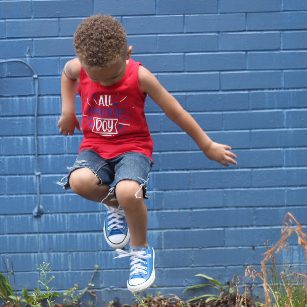 Little boy jumping wearing a red toddler tank that says All American Boy in white and blue