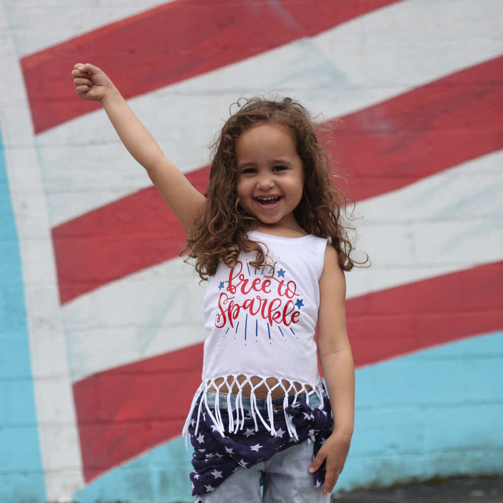 Little girl wearing white Free to Sparkle fringe tank standing in front of American flag mural
