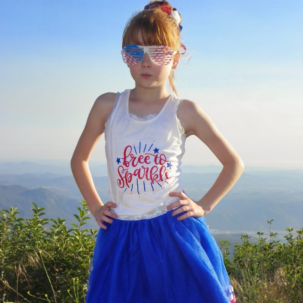 Girl wearing white racerback tank with free to sparkle in red and blue