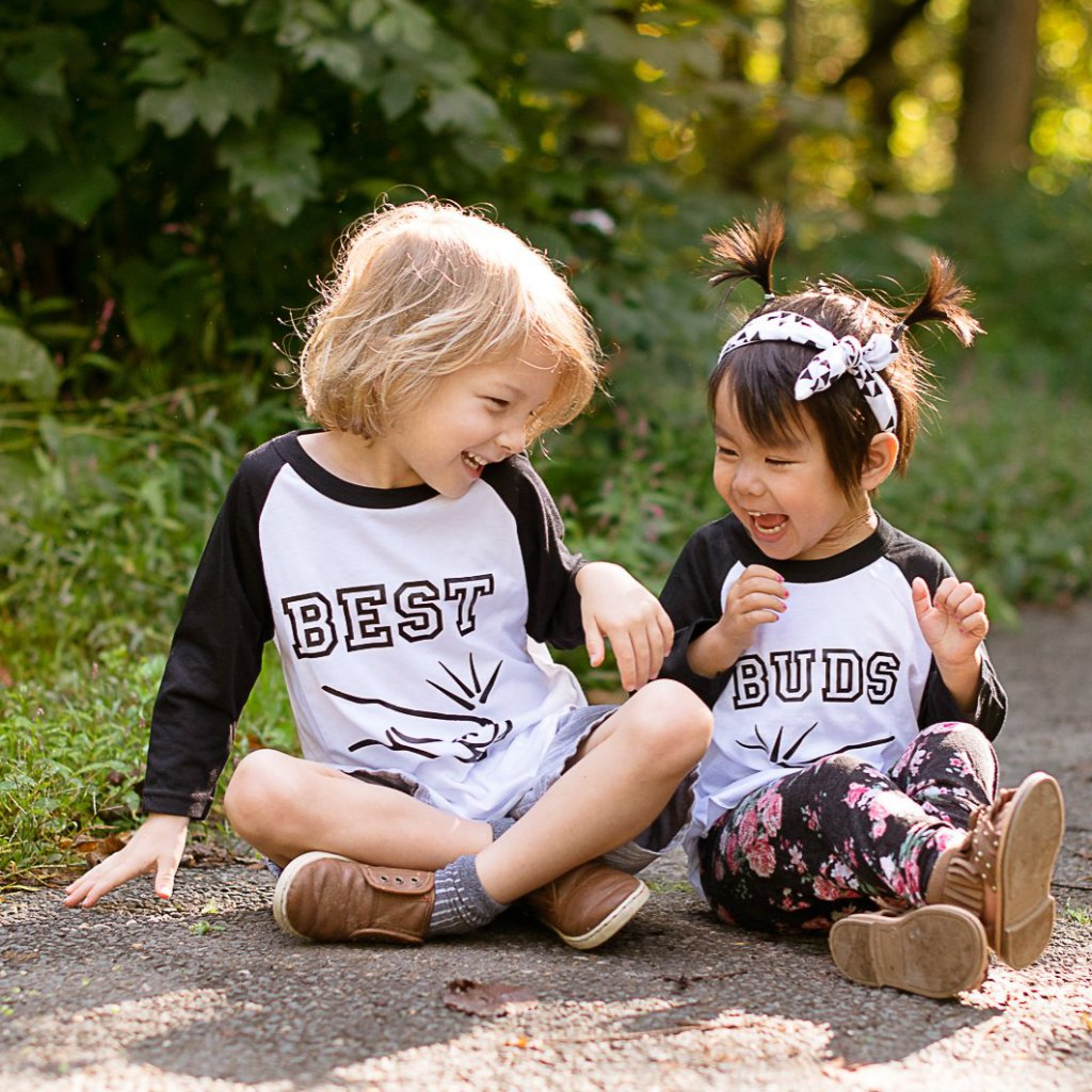 Little boy and girl sitting wearing black sleeve best buds fist bump raglan shirt set