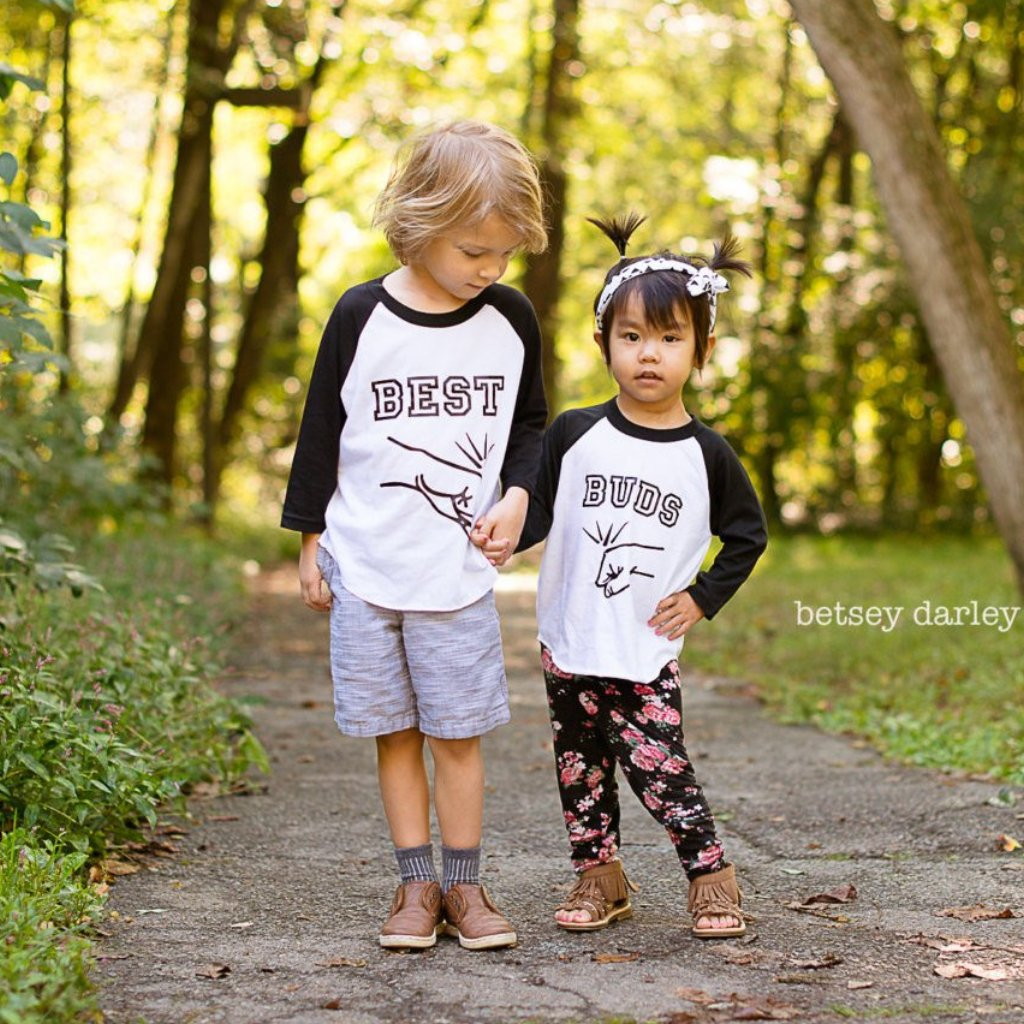 Little boy and girl wearing black sleeve raglans with Best Buds Fist bump designs on them
