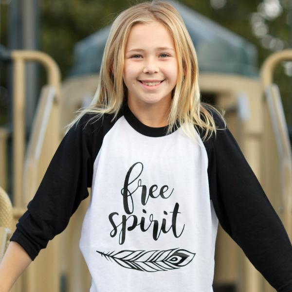 Little girl wearing black sleeve raglan that says Free Spirit with feather below words in black