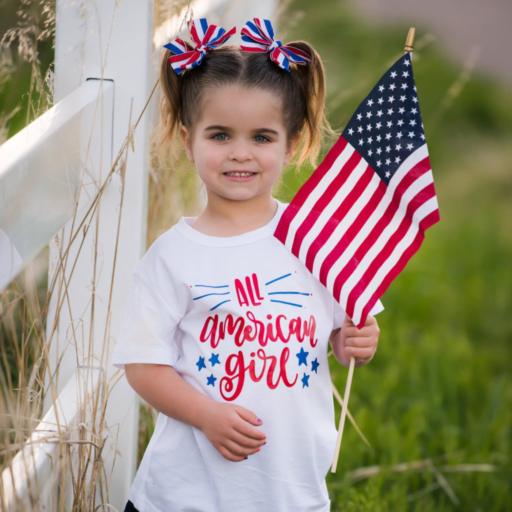 Little girl holding American flag wearing white shirt with All American Girl in red with blue stars