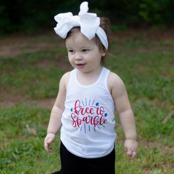 Toddler girl wearing white free to sparkle racerback tank with red and blue writing