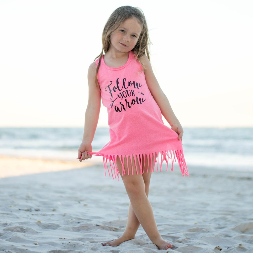 Girl on beach wearing pink fringe dress with follow your arrow in black